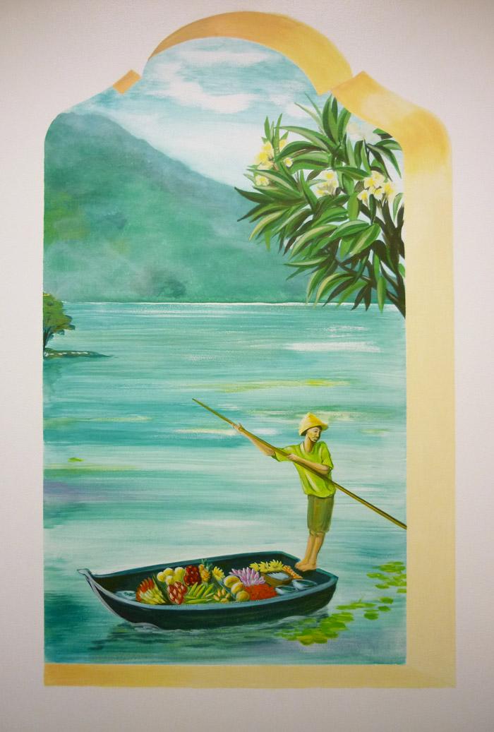 Un jeune garçon sur sa barque chargée de fruits,