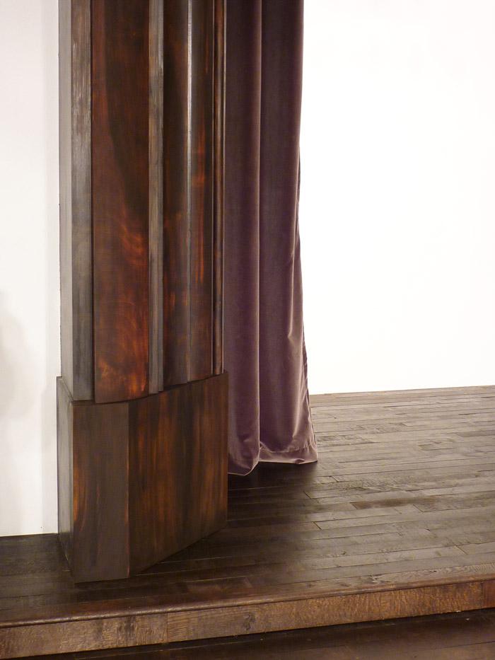 Un bois chaleureux et un rideau sombre pour encadrer les mannequins.